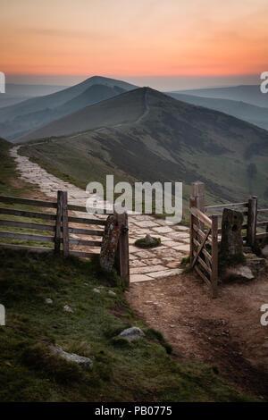 Sunrise view from Mam Torr looking through open gate along mountain ridge - Stock Photo