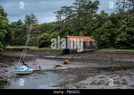 Westport, Ireland -- July 14, 2018. Two boats are anchored in the mud after a long period without rain leaves the river dried up. - Stock Photo