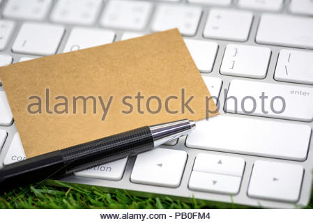 Office memo paper note concept, Brown Eco-friendly paper on white computer keyboard with pen on green - Stock Photo