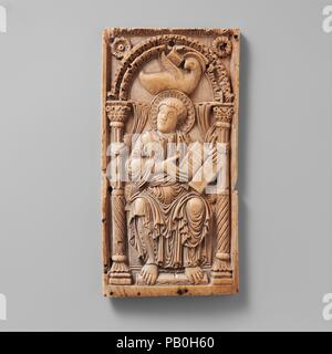 Plaque with Saint John the Evangelist. Culture: Carolingian. Dimensions: Overall: 7 3/16 x 3 11/16 x 1/4 in. (18.3 x 9.4 x 0.7 cm). Date: early 9th century.  The Evangelist, accompanied by his symbol, the eagle, displays the opening text of his gospel. The deep layering of his tunic folds adds life and vigor to the Classical drapery forms. The roughly lettered inscription on the upper border, added at an early date, translates: 'The word of John soars to heaven like an eagle.' This plaque once was thought to be from a book cover, but it is now argued that this panel and three more, which repre - Stock Photo
