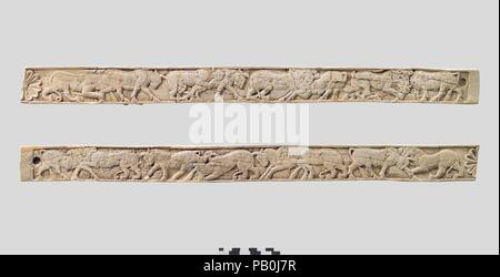 Furniture plaques carved in relief with animal combat. Culture: Assyrian. Dimensions: H. 1 3/4 x W. 21 3/4in. (4.4 x 55.2cm). Date: ca. 8th century B.C..  These long ivory strips were found in a storage room in Fort Shalmaneser, a royal building at Nimrud that was used to store booty and tribute collected by the Assyrians while on military campaign. Since the wooden frame to which the ivory panels were attached had disintegrated, it was not possible to fully reconstruct the piece of furniture to which they belonged. They were probably part of a bed or couch, judging from the large panel associ - Stock Photo