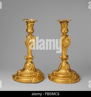 Pair of candlesticks. Culture: French, Paris. Dimensions: Height (each): 11 3/4 in. (29.8 cm); Diam. of base (each): 6 1/2 in. (16.5 cm). Maker: Manner of Juste Aurèle Meissonnier (French, Turin 1695-1750 Paris). Date: 1735-50.  These candlesticks are freely adapted from the same design by Meissonnier as the candlestick in front of them. The different surface treatments, however--punched and matted or smooth and burnished--would have resulted in different reflections of light. Museum: Metropolitan Museum of Art, New York, USA. - Stock Photo