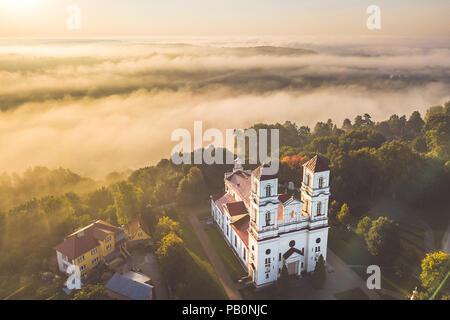 Aerial view of church in foggy morning. Raudondvaris, Kaunas county, Lithuania - Stock Photo