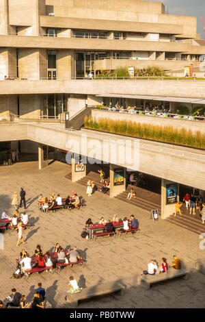 Tourists and locals enjoying a hot July evening outside the concrete Brutalist architecture of the National Theatre in London, UK - Stock Photo