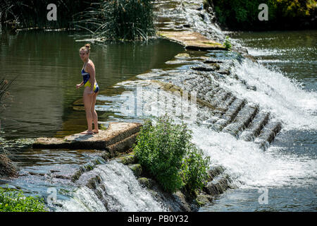 A woman cools off on the weir at Bathampton Mill on the river Avon near Bath in Somerset as temperatures continue to soar across the UK. - Stock Photo