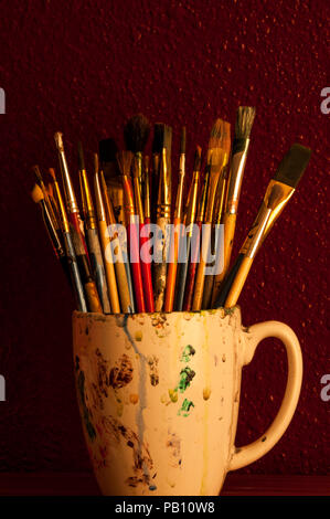 Multicolored paint brushes in coffee mug, still life with sunlight. - Stock Photo