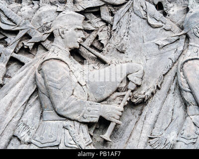 A detail of the Scottish American Memorial in Princes Street Gardens, Edinburgh, Scotland, United Kingdom, showing a kilted bag piper. - Stock Photo