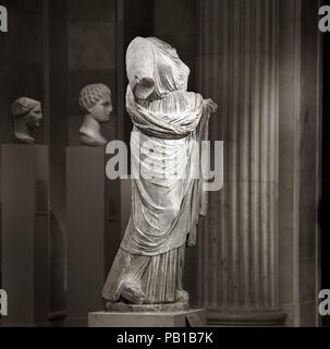Marble statue of a woman. Culture: Greek. Dimensions: Overall (H. w/ plinth): 68 1/8 in. (173 cm)  H. (H. without plinth): 66 1/8 in. (168 cm). Date: 2nd half of the 4th century B.C..  The lively, varied manner in which the texture of the clothing is rendered suggests that this is a Greek original rather than a Roman copy. The crinkly linen of the chiton and the heavier wool of the himation (cloak) are carefully differentiated, and horizontal press folds add variety to the latter's surface. The drilled holes on the sleeves once held metal buttons. The upper part of the chiton is kept firmly in - Stock Photo