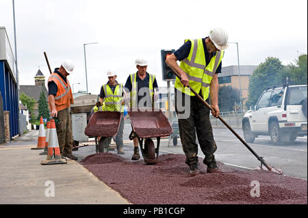 A group of workmen wearing high vis jackets and hard hats are pouring red ashphalt from wheelbarrows on to the road - Stock Photo