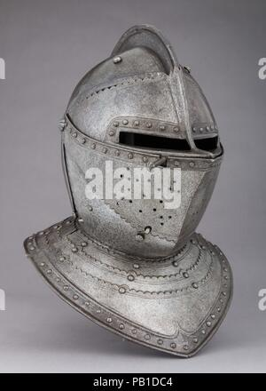 Close-Helmet for the Field. Culture: French. Dimensions: H. 15 3/4 in. (40 cm); W. 11 3/8 in. (28.9 cm); D. 14 5/8 in. (37.1 cm); Wt. 13 lb. 14 oz. (6293 g). Date: ca. 1620-30.  The two-piece construction of the helmet bowl, the scalloped edges of the plates, and the distinctive snub-nosed profile of the visor recall French helmets of about 1620-30. The reinforcing shot-proof plates screwed to either side of the bowl, which add 3 pounds 10 ounces (1675 g) to the overall weight, are rare on close-hlemets for cuirassiers. Beneath the reinforces, the original smooth blue-black surface of the bowl - Stock Photo