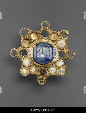 Star-Shaped Brooch with Intaglio. Culture: Ottonian (Rhineland (?)) (setting); Byzantine (intaglio). Dimensions: Overall: Diam. 4 11/16 x 3/4 in. (Diam.11.9 x 1.9 cm). Date: ca. 950-1000 (setting); 337-50 (intaglio).  Jewels conveived as microarchitecure are one of the distinctive hallmarks of Ottonian goldsmiths' work. This brooch is compopsed of a series of arcaded gold cells, linked together to form a star, but its definite horizontal and vertical axes, in fact, make it cross shaped. Because the brooch was buried some gems are missing. Although most of the spaces between the arms of the cro - Stock Photo