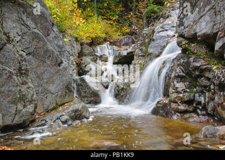 Flume Cascade in Hart's Location, New Hampshire during autumn months. This waterfall is roadside along Route 302 in Crawford Notch State Park. - Stock Photo