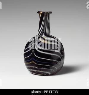 Glass mosaic perfume bottle. Culture: Roman. Dimensions: Diam.: 4 in. (10.2 cm). Date: 1st half of 1st century A.D..  Translucent deep cobalt blue, with translucent honey brown, opaque white, opaque light blue, and opaque yellow trails.  Everted, rounded rim; cylindrical neck, expanding slightly downward, with fine indent around base; globular body; concave bottom.  Striped mosaic pattern of applied trails wound round on a blue ground and then tooled in four strokes, alternating upward and downward, into a broad feather pattern.  Broken and repaired, with one large chip in rim, and one hole an - Stock Photo
