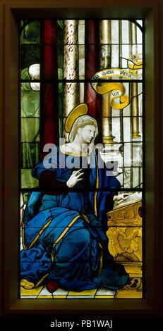 The Annunciate Virgin (one of a pair). Culture: French, Paris. Dimensions: Overall: 64 × 28 in. (162.6 × 71.1 cm). Date: 1552.  Kneeling at her prayer desk, Mary raises her hand in surprise as Gabriel informs her that she will be the mother of the Messiah. The opening of his salutation to her, 'Hail, Mary, full of Grace,' is partially inscribed in Latin on the scroll above her. The composition and the classicizing, slightly elongated figures were derived from a work by Raphael (1483-1520) that was widely known through prints. The windows were made after the same cartoon used for an Annunciatio - Stock Photo