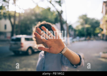 Beautiful young woman covering face with her palm saying no. Female standing outside on city street refusing proposal and making stop gesture with her - Stock Photo
