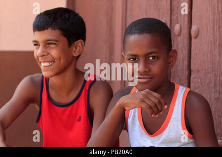 Two young boys sitting in the street, Trinidad, Cuba - Stock Photo