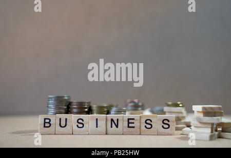 Business Word Written In Wooden Cube on wood table with money graph in background - Stock Photo