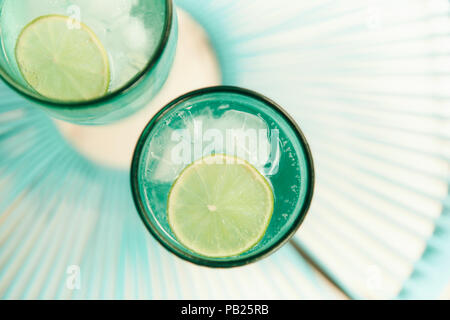 A couple of refreshing fizzy drinks with lime slices in summer. - Stock Photo