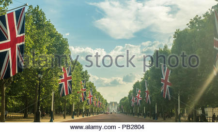 Union Jack Flags lining The Mall looking towards The Queen Victoris Memorial in front of Buckingham Palace, London, England - Stock Photo