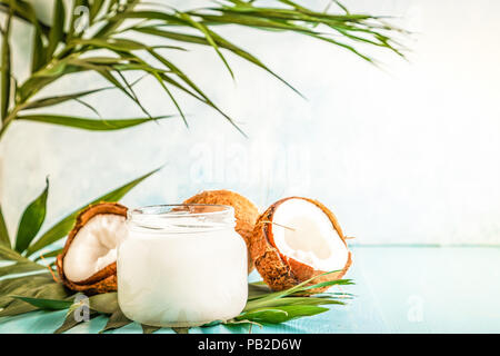 Coconut oil and coconuts on a bright pastel background, selective focus. - Stock Photo