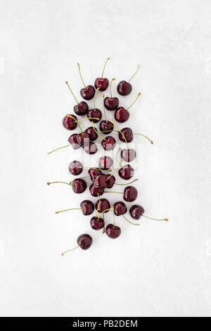 Top view of sweet red cherries on white textured and patterned background with copy space. - Stock Photo