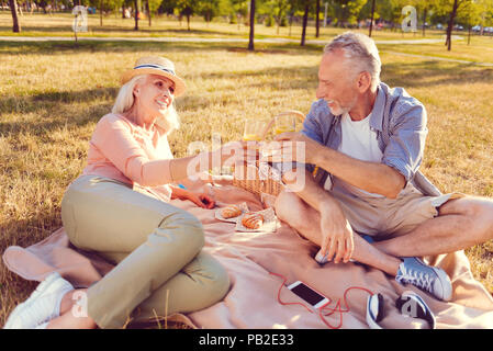 Relaxed retired couple going out for picnic - Stock Photo