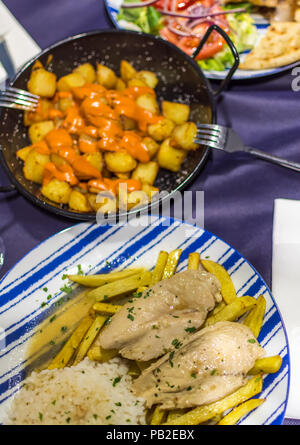 Lemon chicken with homemade fries, patatas bravas (Spanish fried potatoes) and chicken gyros with homemade chips and vegetable salad. - Stock Photo
