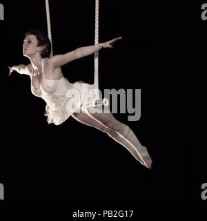 Circus performer balancing on a trapeze - Stock Photo