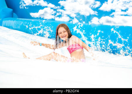 Young girl on water slide at aquapark. Summer holiday. - Stock Photo