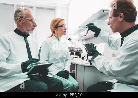 Professional bioengineer teaching his partners - Stock Photo