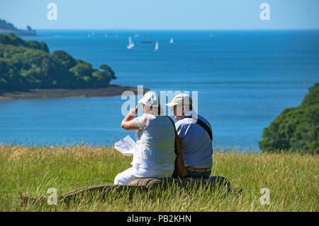 senior couple resting overlooking falmouth bay in cornwall, england, britain, uk. - Stock Photo