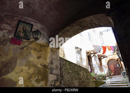 Pretty Italian village. Characteristic alley with a sacred image of the Virgin Mary and hanging clothes - Stock Photo