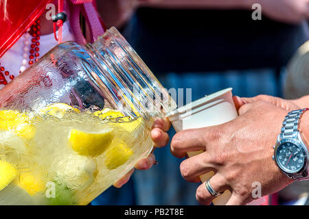 Woman in beads pours cold water with ice and carved lemons from a glass bottle into a glass for man with a ring and a clock on his hand - Stock Photo