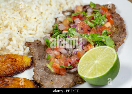 A steak covered in pico de gallo surrounded by plantains and white rice on a white plate. Cuban food. - Stock Photo