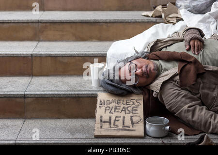 sleeping beggar rest on pathway and wait of money donation from another people in business zone downtown in city, concept of poor, donation, homeless  - Stock Photo