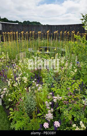 Beautiful show garden (natural planting, colourful meadow flowers, tractor sculpture) - John Deere Garden, RHS Chatsworth Flower Show, England, UK. - Stock Photo