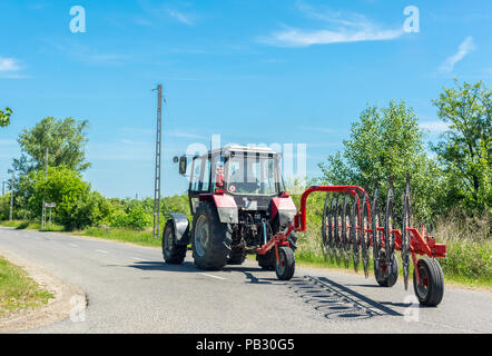 Tractor with hay tedder on rural road on sunny day - Stock Photo