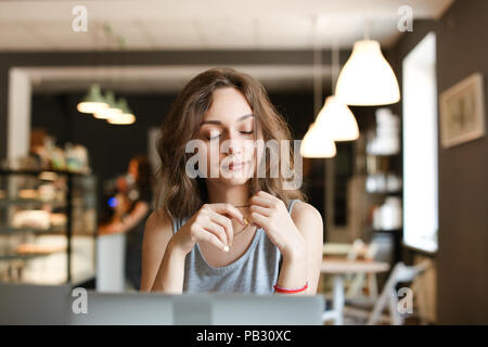 Young girl making video call by laptop at cafe. Concept of social netwrorks and modern technology. - Stock Photo