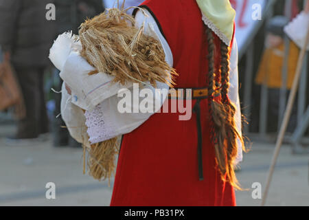 Unrecognizable woman with long braids and traditional costume brings golden wheat classes during harvest festival. Harvest celebration time. - Stock Photo
