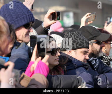 A crowd of people use different types of smart phones and tablets to take a pictures of interesting things . Many phones in one place. smart devices a - Stock Photo