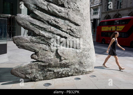 Londoners walk past the sculpture entitled City Wing on Threadneedle Street in the City of London, the capital's financial district, on 25th July 2018, in London, England. City Wing is by the artist Christopher Le Brun. The ten-metre-tall bronze sculpture is by President of the Royal Academy of Arts, Christopher Le Brun, commissioned by Hammerson in 2009. It is called 'The City Wing' and has been cast by Morris Singer Art Founders, reputedly the oldest fine art foundry in the world. - Stock Photo