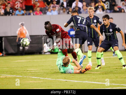 East Rutherford, USA. 25th July, 2018. Liverpool's Sadio Mane (L) passes through Manchester City's goal keeper Joe Hart during the International Champions Cup match at MetLife Stadium in East Rutherford of New Jersey, the United States, July 25, 2018. Credit: Wang Ying/Xinhua/Alamy Live News - Stock Photo