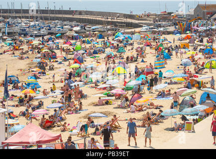 Lyme Regis, Dorset, UK. 26th July 2018.  UK Weather:  Hot sunshine and blue sky in Lyme Regis. Families and sunseekers flock to the picturesque beach at the seaside resort of Lyme Regis to enjoy the scorching hot sunshine again this afternoon as the UK melts.  Temperatures are on the rise again with Friday set to be the hottest day on record. Credit: Celia McMahon/Alamy Live News - Stock Photo