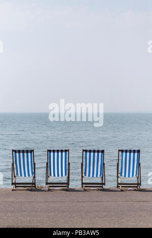 Four Unoccupied Traditional Style Deckchairs on Seafront at Westcliff-on-Sea During Heatwave of July 2018 - Stock Photo