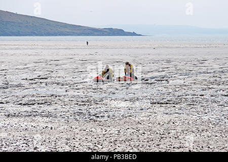 Weston-super-Mare, UK. 26th July, 2018. Coastguards rescue a man who had become trapped on the mud flats below the beach. Weston-super-Mare is situated on the Severn estuary, which has the second-highest tidal range in the world, and people often become trapped in the large areas of dangerous soft mud which are exposed at low tide. Keith Ramsey/Alamy Live News - Stock Photo