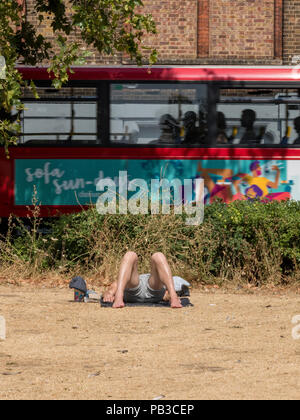London, UK. 26th July, 2018. UK Weather. Office workers and visitors to London sunbathing in the beautiful sunshine on the hottest day of the year in the city with temperatures of 32 degrees. People lying in the park and spending their break from woek relaxing in the heatwave during the continuing dry spell and hot temperatures. 2018 heatwave. Credit: Steve Hawkins Photography/Alamy Live News - Stock Photo