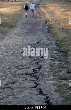 London, UK. 26th July, 2018. People pass by dried land in London, Britain on July 26, 2018. Temperatures in the coming days could break all-time UK records, with the mercury set to soar to 37 degree Celsius, it is forecasted Thursday. Credit: Han Yan/Xinhua/Alamy Live News - Stock Photo