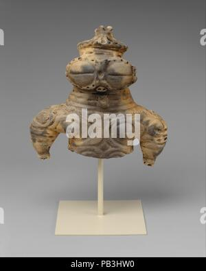 Dogu (Clay Figurine). Culture: Japan. Dimensions: H. 6 1/2 in. (16.5 cm); W. 6 3/8 in. (16.2 cm); D. 3 1/8 in. (7.9 cm). Date: 1000-300 BC.  This stylized, hollow figurine (dogu) of a female is representative of the type found in the Tohoku region of northern Honshu and made during the Late and Final Jomon periods. The most arresting aspect of these figurines is their large bisected coffeebean-shaped eyes. While the true meaning of this convention remains unknown, the eyes are often likened to the snow goggles worn by the Inuit of North America. The nose and mouth are merely suggested by small - Stock Photo