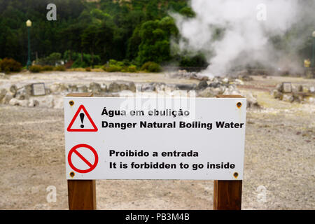 Sign warning of hot, boiling water from hot springs at Furnas, Sao Miguel, Azores - Stock Photo