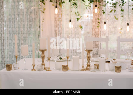 It is a lot of white candles in golden candlesticks of different height. Cozy details on a wedding table - Stock Photo